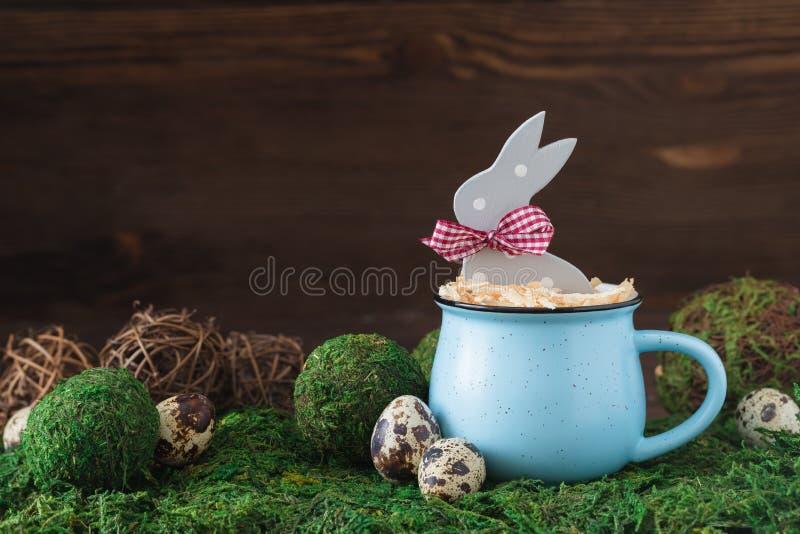 在一个蓝色杯子的木圆点灰色兔子在草背景,复活节明信片概念 图库摄影