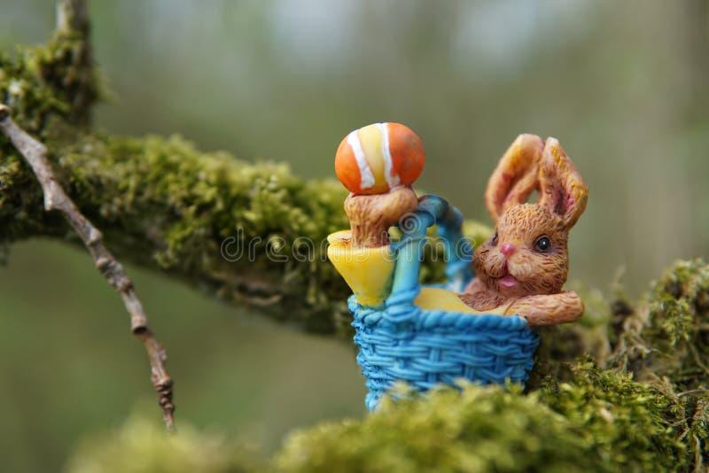 在一个蓝色篮子的复活节兔在树 免版税库存照片