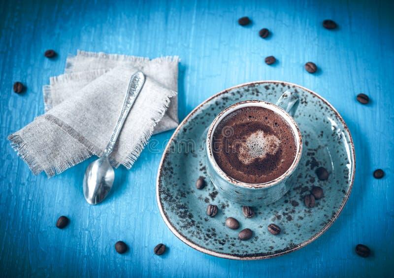在一个蓝色葡萄酒背景的浓咖啡 免版税库存图片