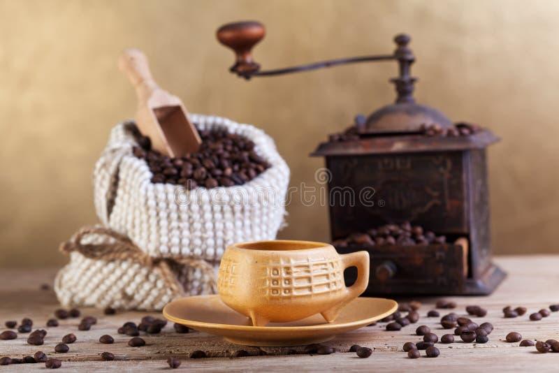 在一个袋子的咖啡豆与研磨机和杯子 免版税库存图片
