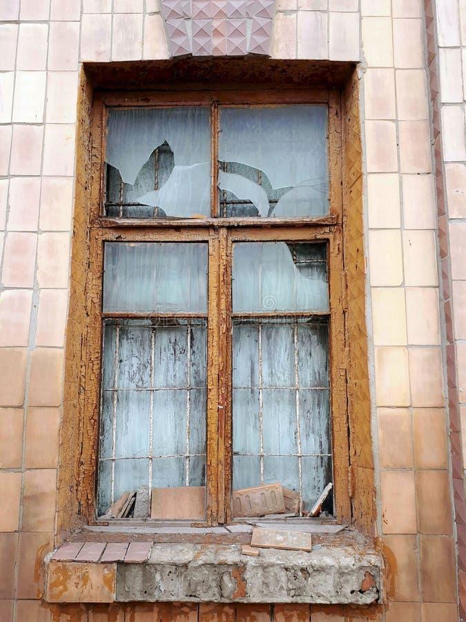在一个被放弃的房子的砖墙上的老残破的窗口 免版税库存图片
