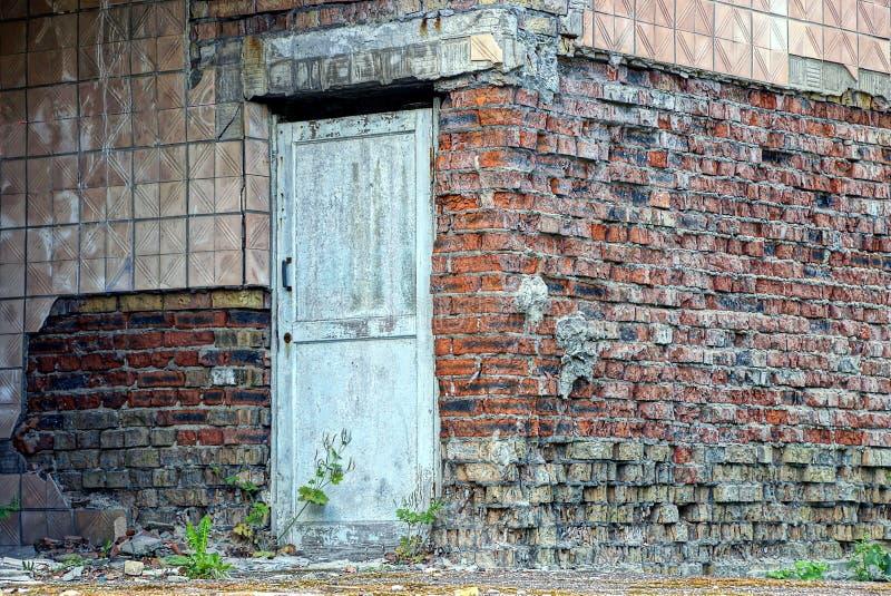 在一个被放弃的砖房子的墙壁上的老灰色门 免版税库存图片