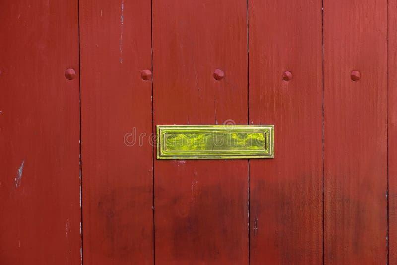 在一个被绘的木门的优美的黄铜邮箱槽孔 免版税库存照片