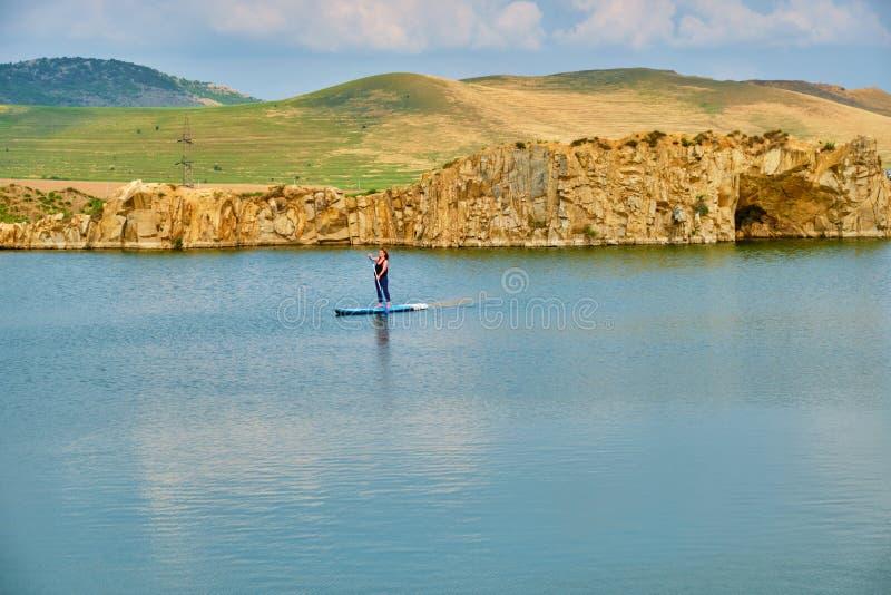 在一个被隔绝的湖的年轻女性旅游桨搭乘,有文本的空间的在底部 Iacobdeal湖在Turcoaia,图尔恰 免版税库存图片