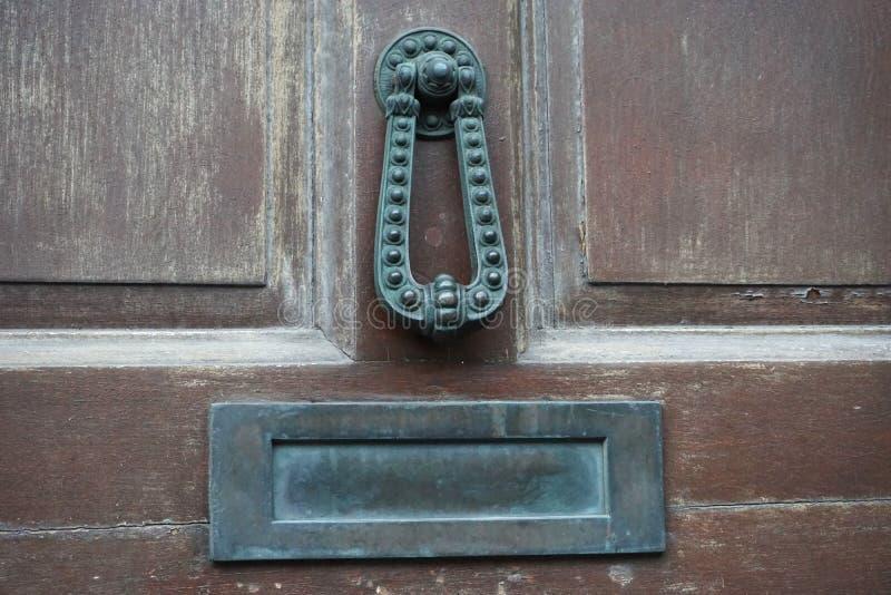 在一个被风化的棕色门的古色古香的古铜色通道门环集合 免版税库存图片