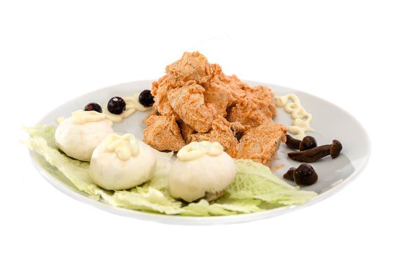 在一个调味汁的炖鸡肉用蘑菇 在白色背景的美丽的盘 免版税库存图片
