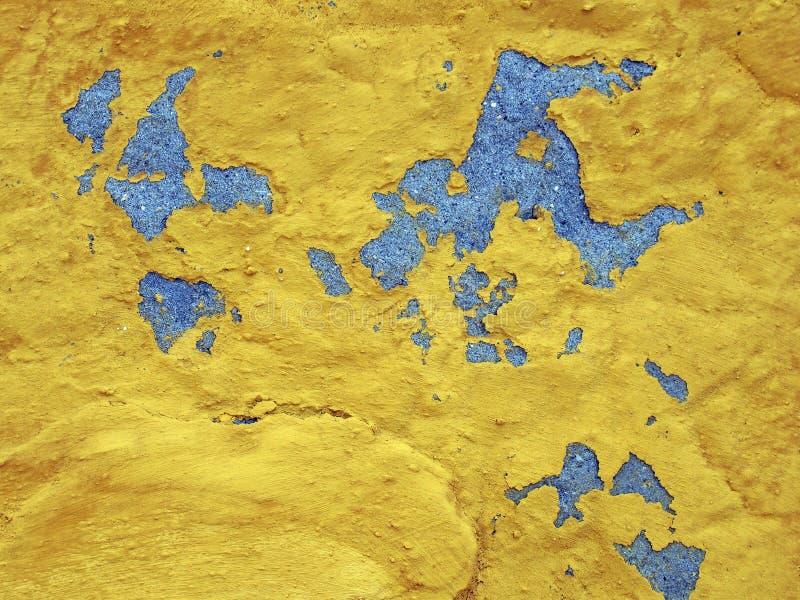 在一个质感粗糙的灰色混凝土墙上的明亮的黄色剥的油漆 库存照片