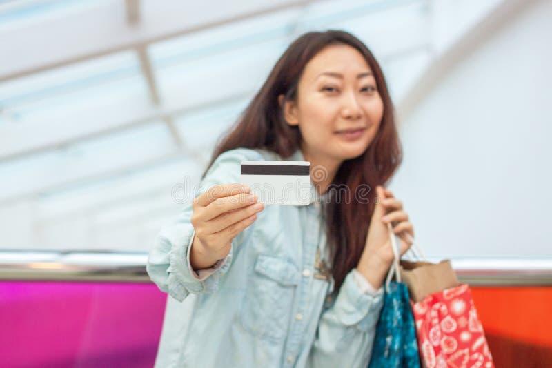 在一个购物中心的年轻亚洲女孩购物与信用卡 拿着口袋和信用卡的美女 免版税库存图片