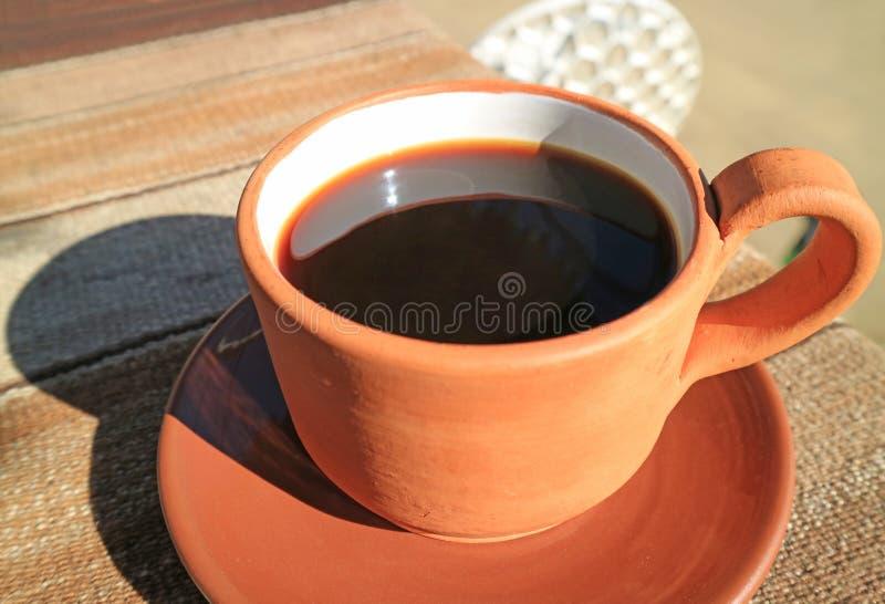 在一个赤土陶器杯子的无奶咖啡在与温暖的阳光的室外大阳台 免版税库存照片