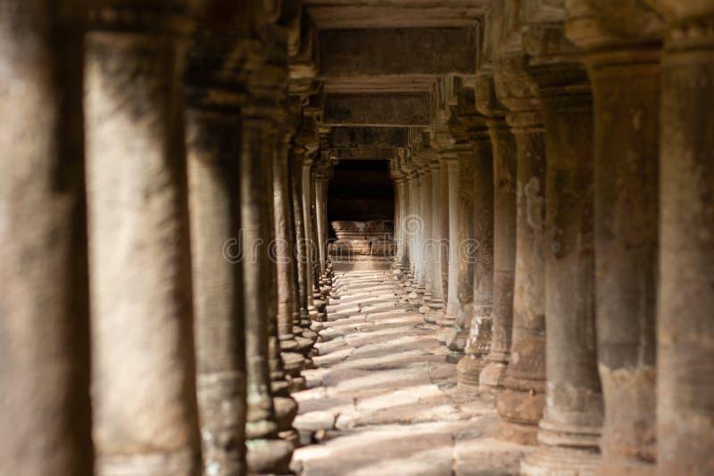 在一个走道下的古庙柱子在吴哥城,柬埔寨 图库摄影