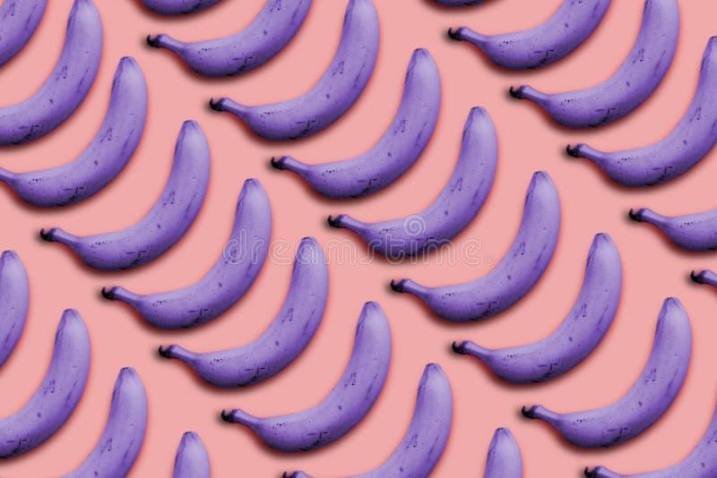 在一个超现实主义的样式紫色香蕉的创造性的想法在桃红色背景 库存图片