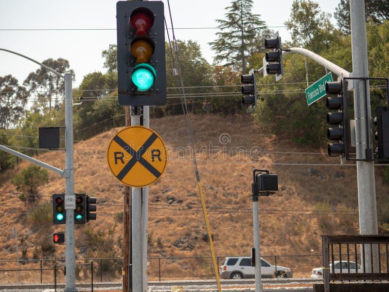 在一个轨道交叉点的平交道口标志在有小山的一条拥挤的街上 免版税库存图片