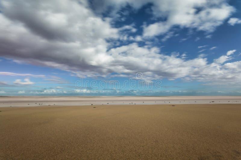 在一个轻轻地倾斜的海滩的海浪与多云天空 免版税库存照片