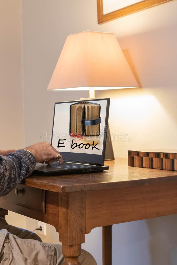 在一个远程读取站点的膝上型计算机屏幕,下载书 免版税库存图片