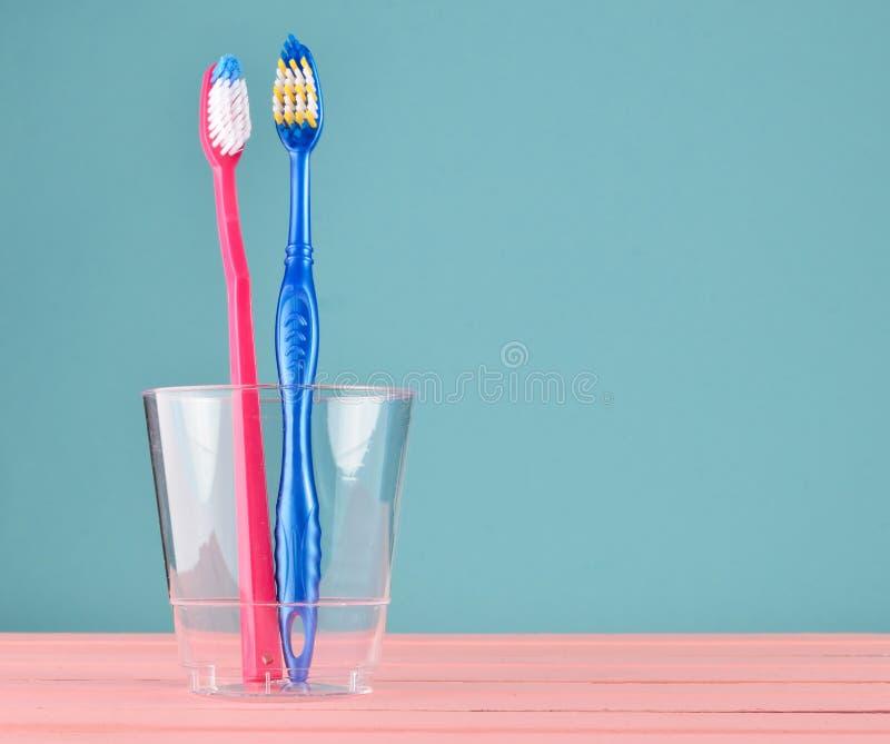 在一个透明塑料杯子的两把牙刷在淡色蓝色背景的,拷贝空间,简单派卫生间里 免版税库存图片