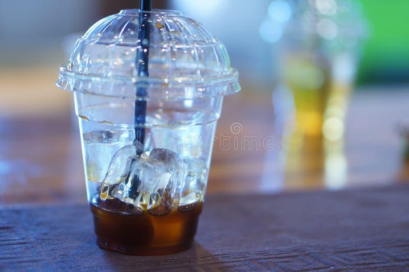 在一个透明塑料杯子的被冰的咖啡有黑秸杆的 免版税库存图片