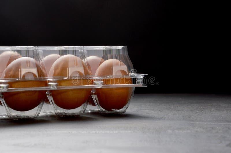 在一个透明塑料盒的红皮蛋在黑背景 库存图片
