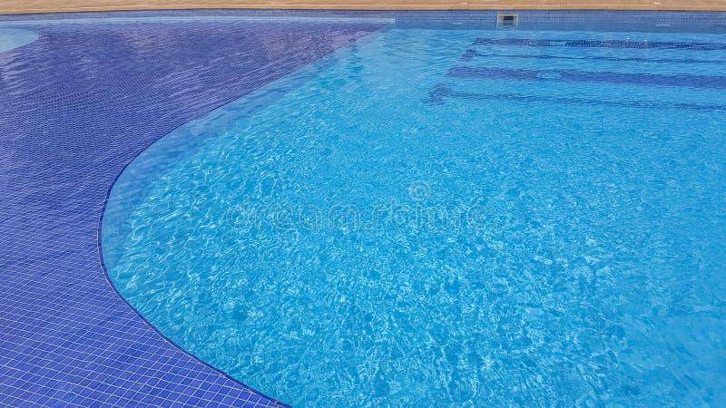 在一个透明水池的看法和与深蓝条纹的蓝色背景 免版税库存图片