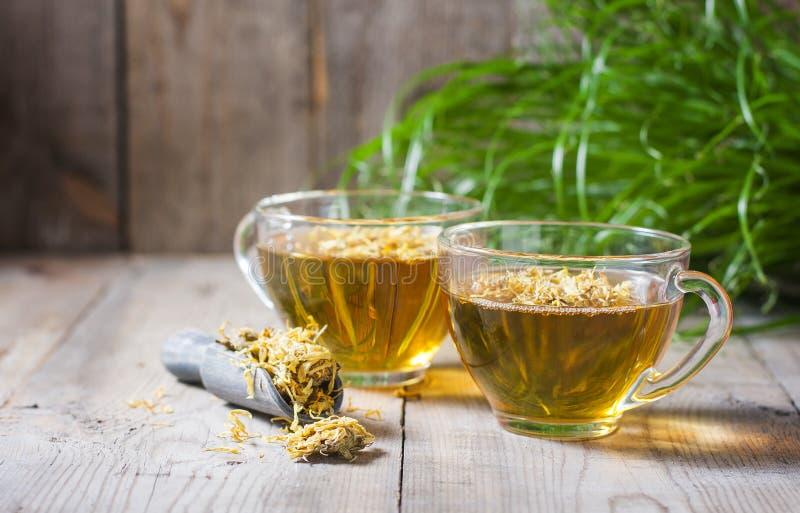 在一个透明玻璃杯子的清凉茶有在木背景的金盏草花的 Phytotea 免版税图库摄影