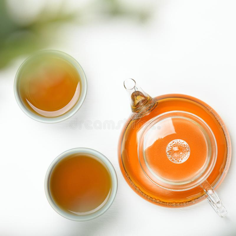在一个透明茶壶和小杯子的绿茶在以绿色植物为背景的一张白色桌上 有用 库存图片