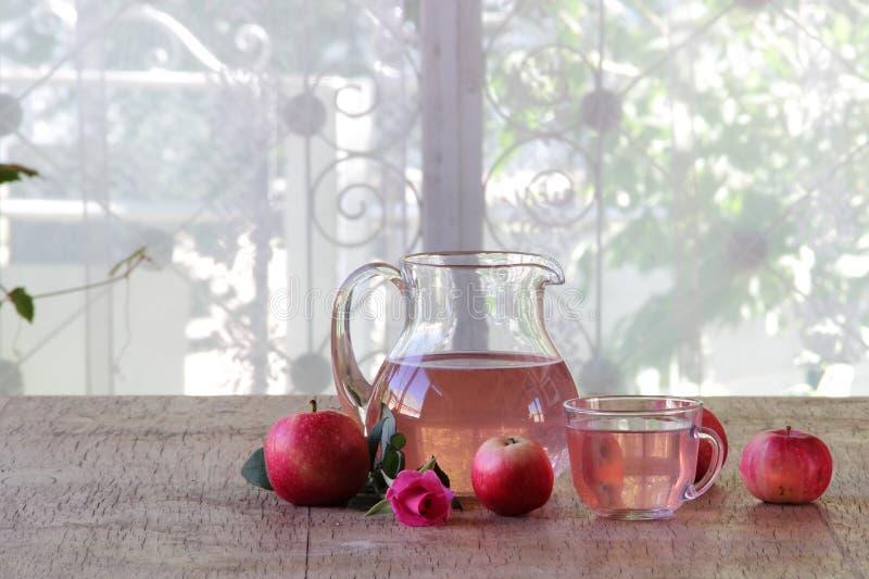 在一个透明水罐、新鲜的苹果和玫瑰的苹果计算机蜜饯 库存图片