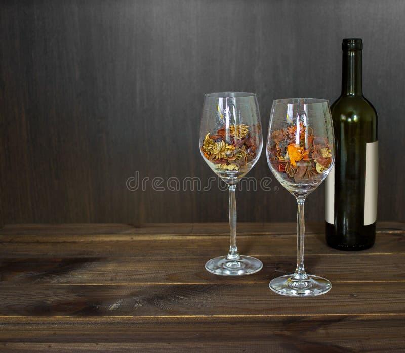 在一個酒杯和酒瓶的秋葉在木桌背景圖片