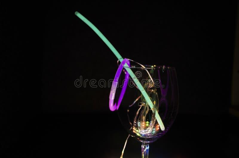 在一个酒杯的蓝色和绿色焕发棍子与从表面aginst的五颜六色的轻的relection黑暗的背景党 免版税库存照片
