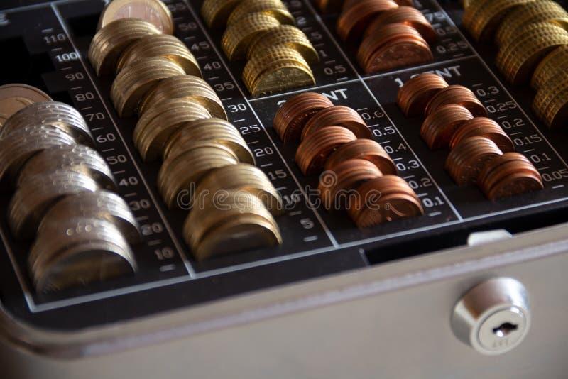 在一个金属现金箱子的被堆积的硬币有锁的 库存照片
