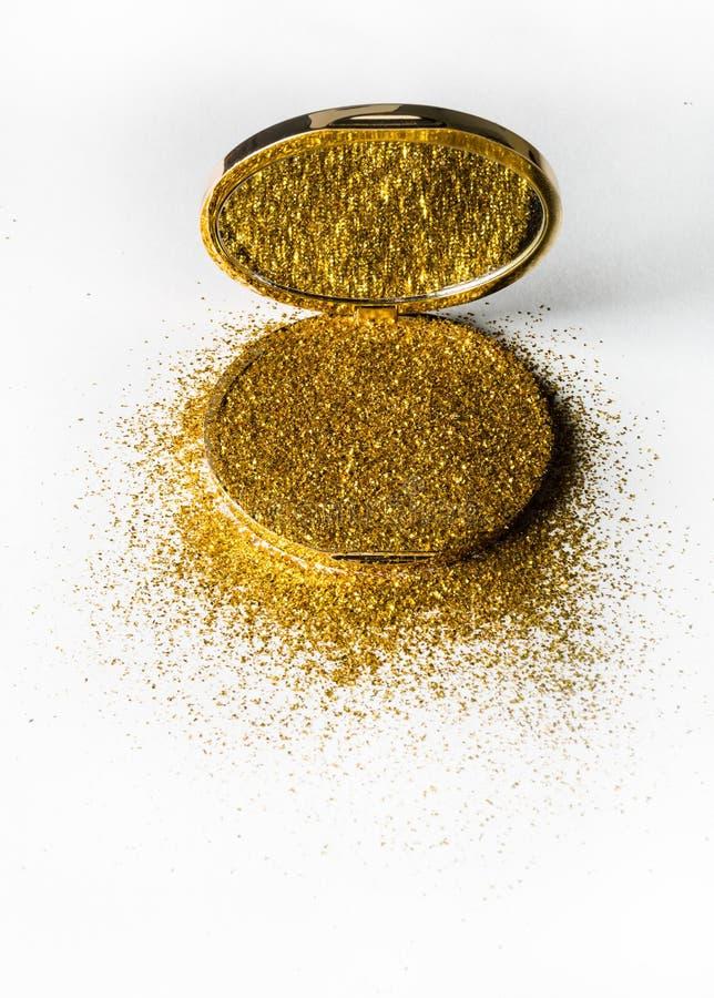 在一个金粉末箱子的粉末轮廓色_有在镜子反映的金闪闪发光的 背景查出的白色 库存图片