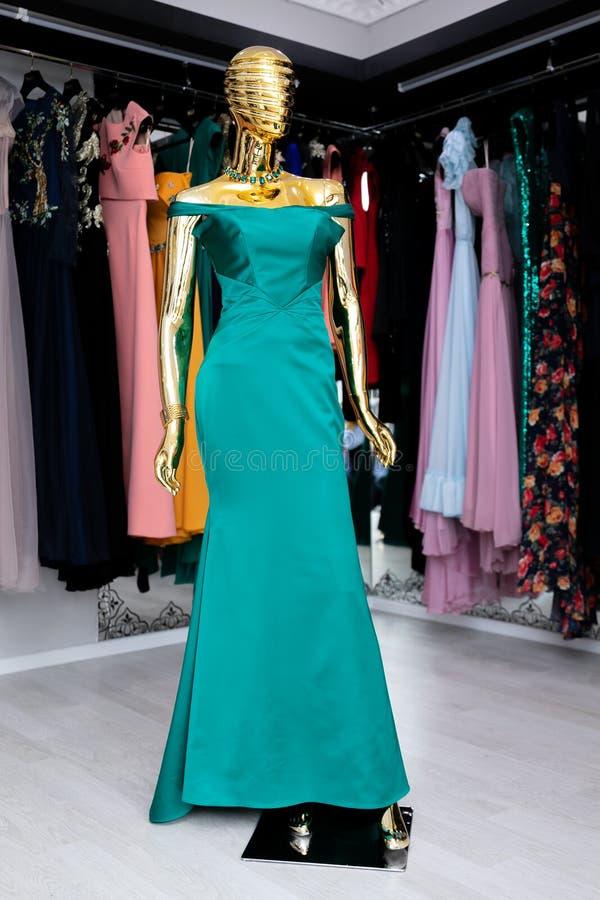 在一个金黄时装模特的女性,长的绿松石礼服 图库摄影