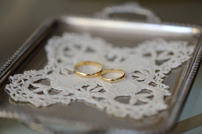 在一个银色盘子的两只金戒指 免版税库存图片