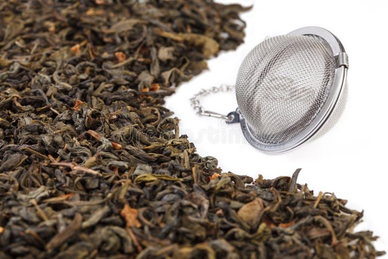 在一个链子的滤茶器,当干绿色大叶子茶混合物用刺番荔枝,被隔绝在白色背景 库存照片