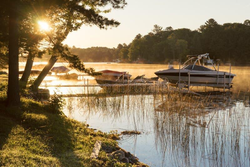 在一个镇静湖的有薄雾的早晨日出 免版税库存图片