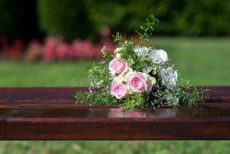 在一个长木凳的新娘花束 免版税库存照片