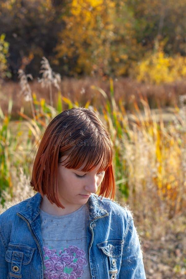 在一个阳光明媚的日子里,一个女孩低着头站在秋雨林的背景下 免版税库存照片