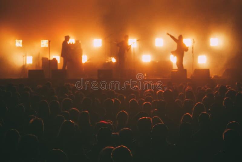 在一个阶段的摇滚乐队在人群前面的背后照明 库存图片
