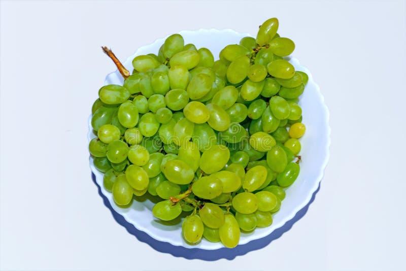在一个陶瓷碗的新鲜的绿色和淡黄色葡萄在白色背景 库存照片