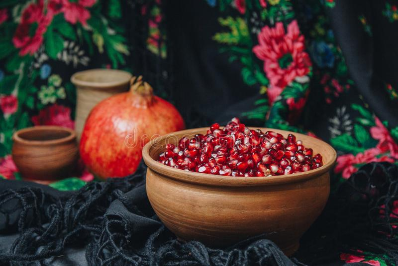 在一个陶瓷碗的石榴五谷在葡萄酒织品背景,石榴果子,陶瓷水罐,陶瓷板材,种族披肩, 库存图片