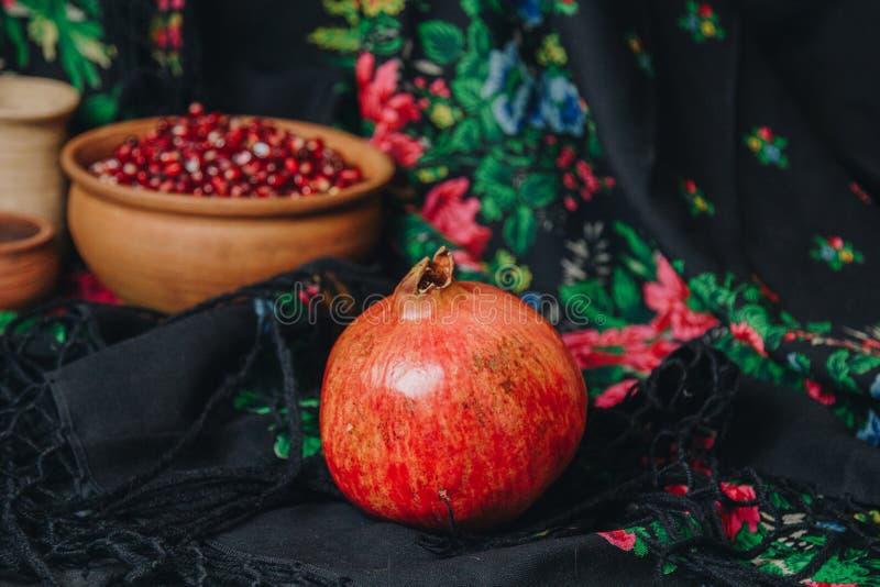 在一个陶瓷碗的石榴五谷在葡萄酒织品背景,石榴果子,陶瓷水罐,陶瓷板材,种族披肩, 库存照片