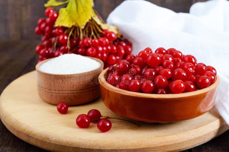 在一个陶瓷碗的红色荚莲属的植物,糖,一束茶的莓果 免版税图库摄影