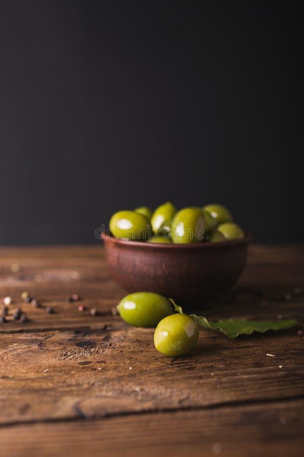 在一个陶瓷碗的绿橄榄在木背景 免版税库存图片
