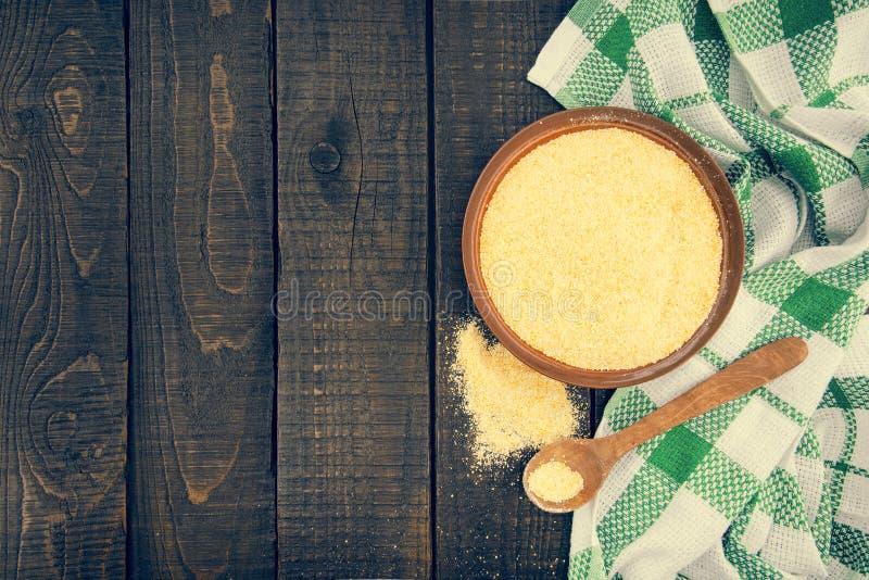 在一个陶瓷碗的黄色玉米粉在一张土气木桌上 意大利传统麦片粥的准备的成份 图库摄影