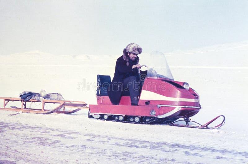 在一个雪上电车玻璃瓶子的苏联金探油矿者运输有机器的上油 免版税库存图片