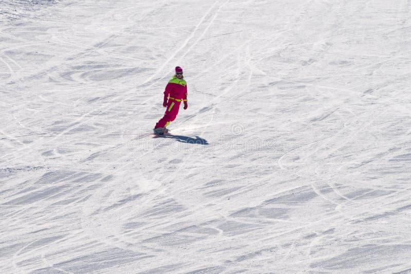 在一个雪板的妇女乘驾在山坡 免版税库存照片