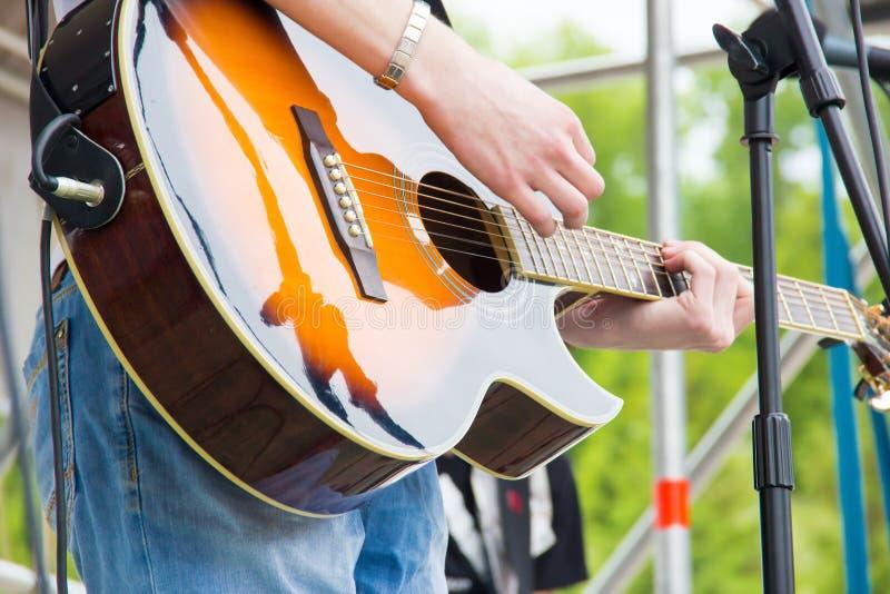 在一个露天节日的音乐带perfom 弹音乐镶有钻石的旭日形首饰的颜色声学吉他的吉他弹奏者人 免版税库存图片