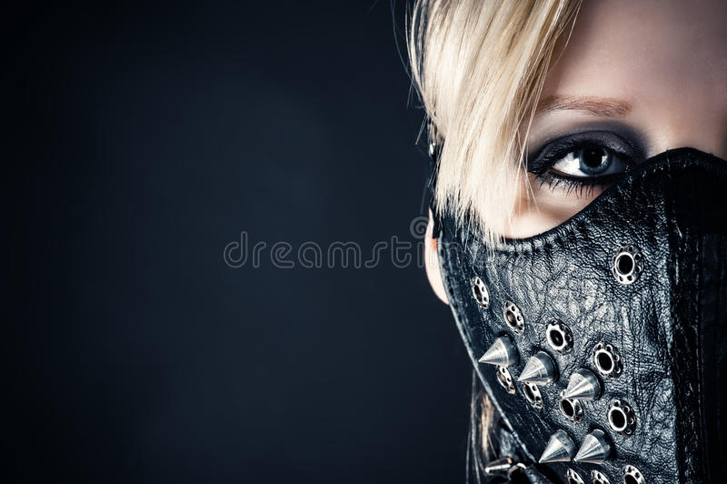 在一个面具的妇女奴隶与钉 库存照片