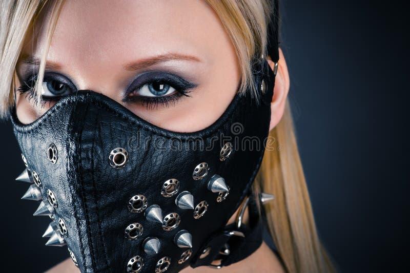 在一个面具的妇女奴隶与钉 免版税图库摄影