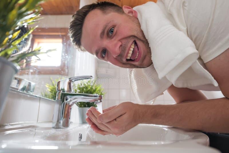 在一个面盆的白种人人洗涤物面孔在白色洗手间 免版税库存图片