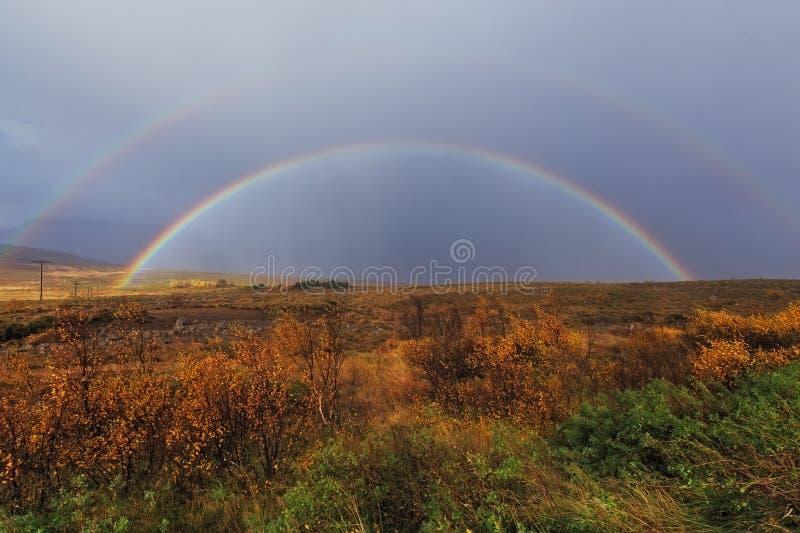 在一个领域的一条双重彩虹在秋天期间的冰岛 库存图片