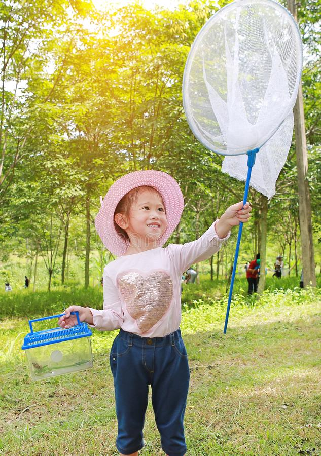 在一个领域的可爱的矮小的亚洲女孩穿戴草帽与昆虫网在夏天 r 库存图片